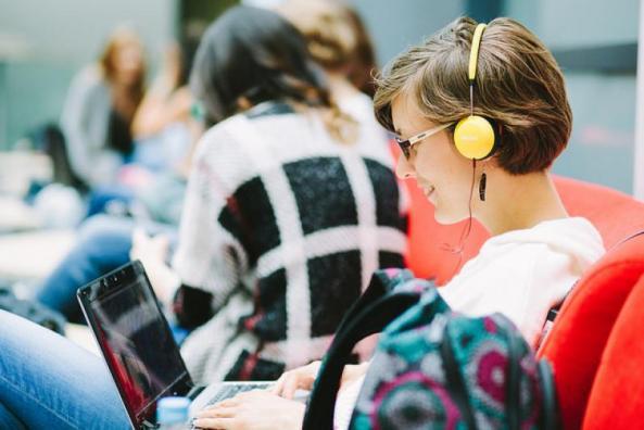 Õppur arvuti ja kõrvaklappidega